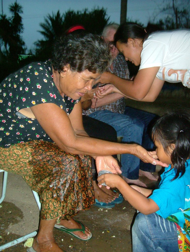 Little girl pouring water over mother's hands for Thai New Year