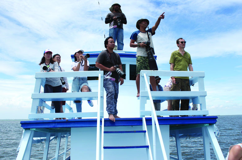 Boat people on whale watching in Thailand tour