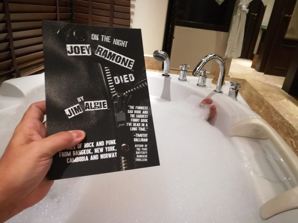 Photo of book cover held by reader in bathtub