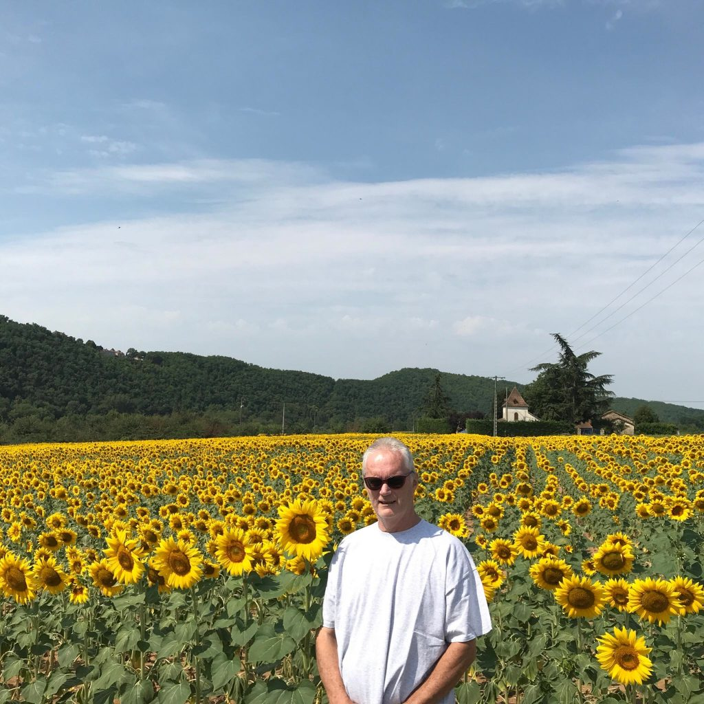 Profile photo of Bangkok 8 author surrounded by sunflowers in rural France.