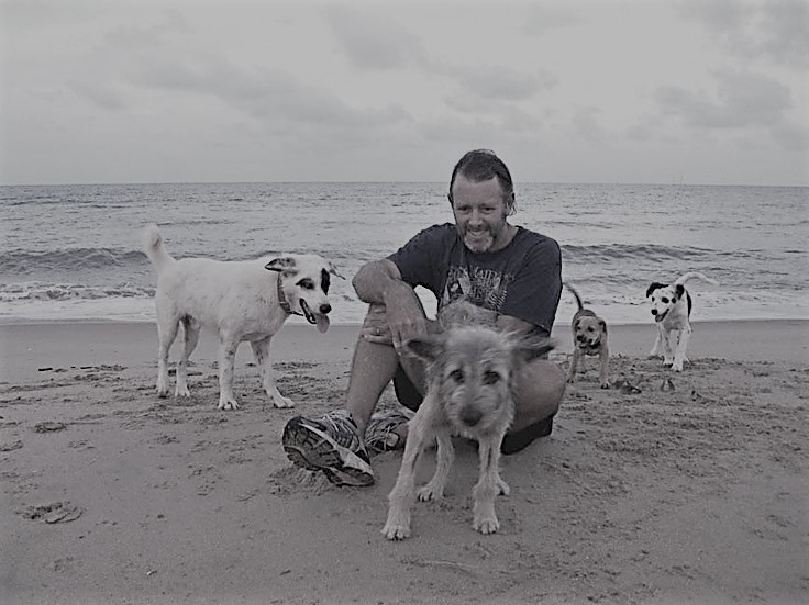 Portrait of author Colin Cotterill with his dogs on a Thai beach